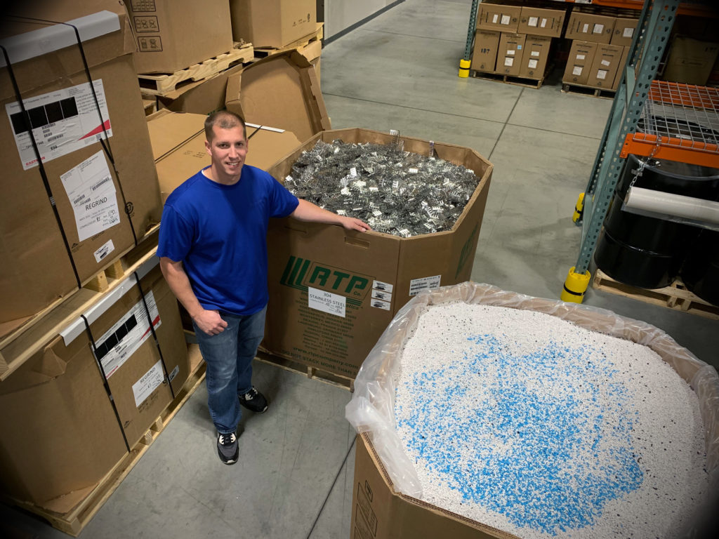 Matt Iverson of Accumold stands beside a gaylord box of resin in the Accumold warehouse